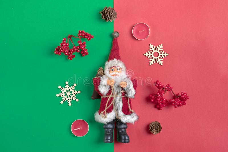 Christmas composition. Christmas decoration gifts, Santa Claus hat , candy, snowflakes on green, red background. royalty free stock photo