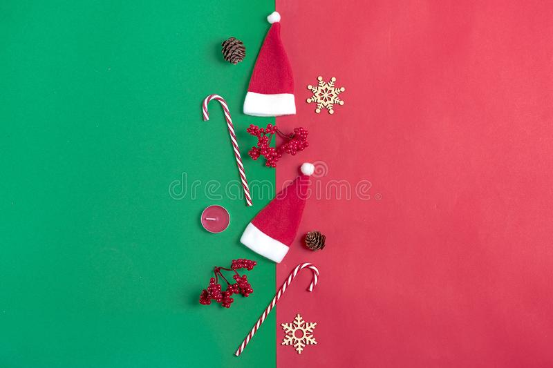 Christmas composition. Christmas decoration gifts, , Santa Claus hat , candy, snowflakes on green, red background. royalty free stock image