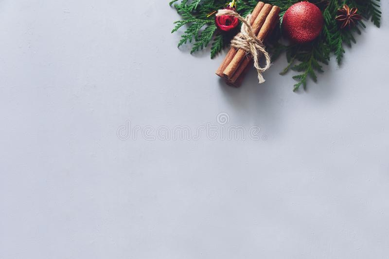 Christmas composition. Christmas fir tree branches, balls, cinnamon sticks and anise stars on gray wooden background. Flat lay. To stock photography