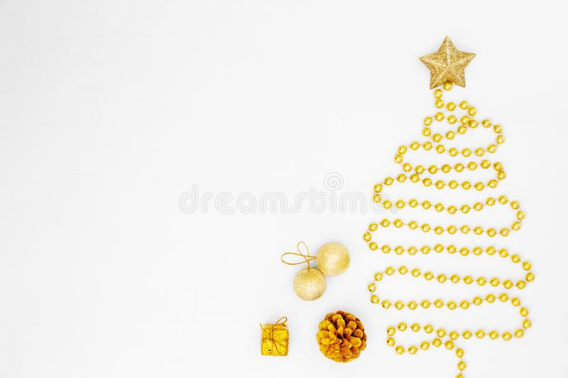 Christmas tree made of gold bead garland with decorations on white background. Christmas composition. Christmas tree made of gold bead garland with decorations stock photos