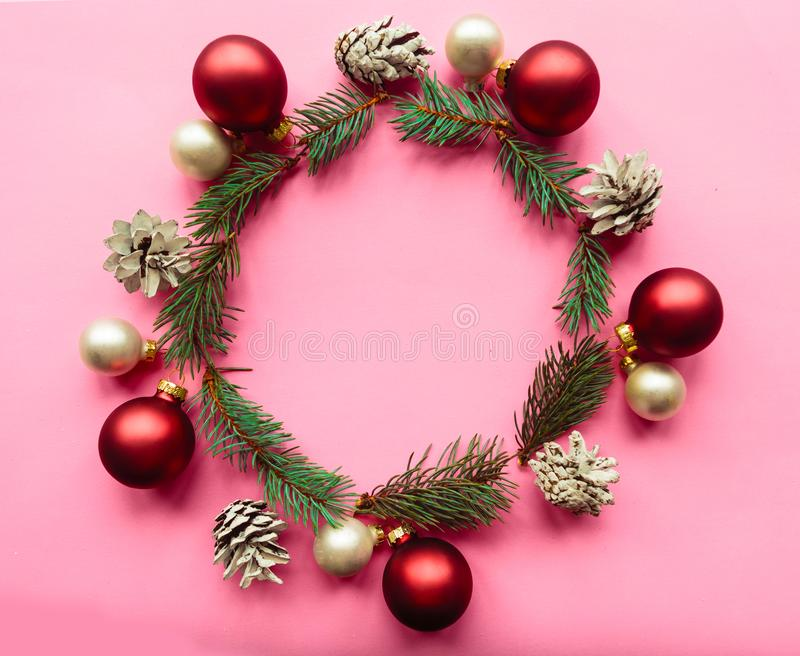 Christmas composition. Christmas wreath with fir branches and red baubles on pink background. Christmas, winter, new year concept. stock images