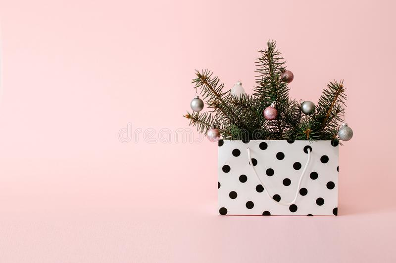 Christmas composition with Conifer Evergreen tree branches and bauble ball in gift bag. Christmas and 2020 new year minimal royalty free stock photography