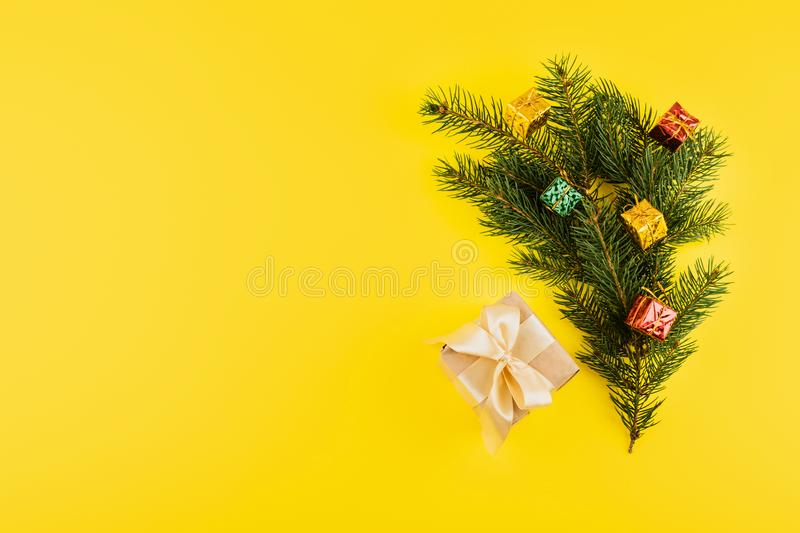 Christmas composition with Conifer Evergreen tree branches and gift box on yellow background. Christmas and 2020 new year minimal. Concept, copy space, flat royalty free stock photo