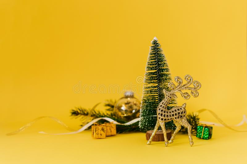 Christmas composition with Conifer Evergreen tree branches, golden deer and christmas toys on yellow background. Christmas and royalty free stock photo