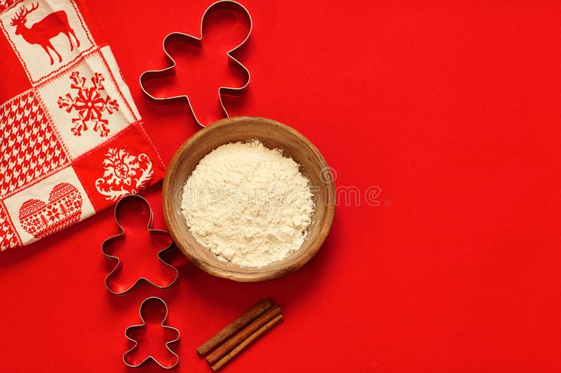 Christmas composition Cookie cutters and a bowl of flour on red background stock photos
