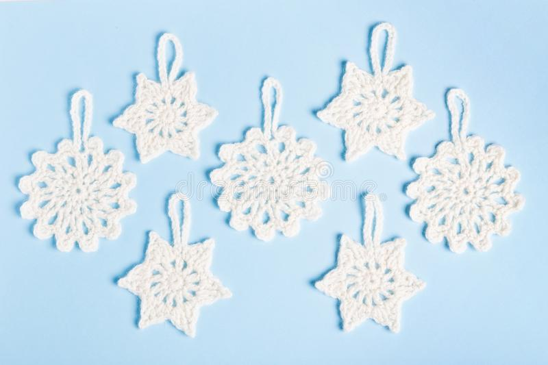Christmas composition of crocheted white snowflakes and stars on blue background. Top view, flat lay, copy space. stock photo