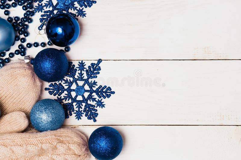 Christmas composition of decorations, blue balls, stars and mittens on wooden white background with copy space. Winter, new year,. Holiday and decor concept stock image