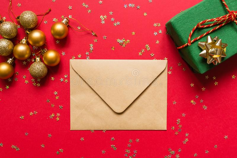 Christmas composition. Envelope, wrapped gift, toys on red background with golden confetti. new year concept. Greeting card, xmas royalty free stock photos