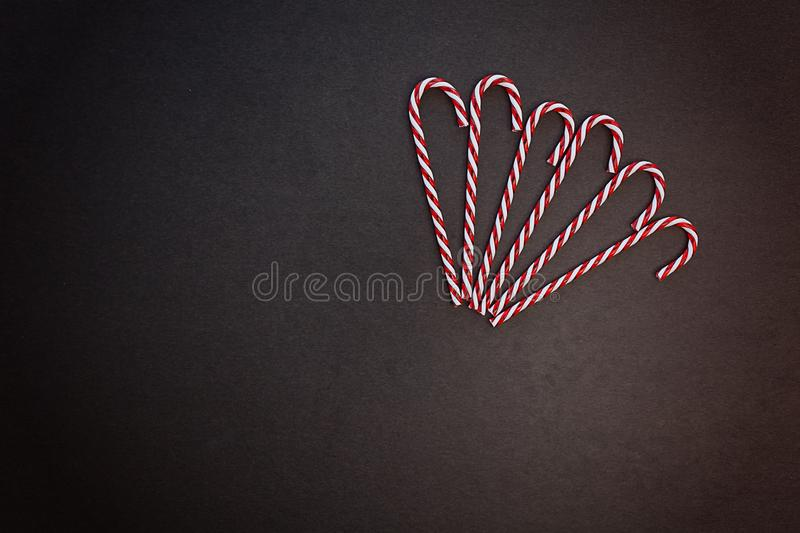 Christmas composition. A fan of caramel striped cane candies on a dark gray background. Minimalist New Year concept for your mockup and project. Flat lay, copy royalty free stock image