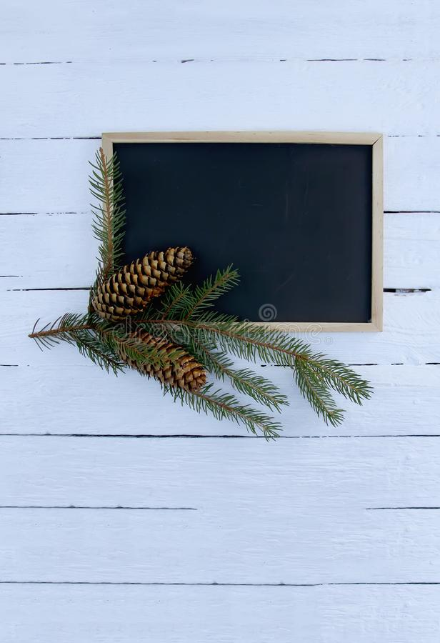 Christmas composition with fir branch and cones on white aged wooden background. New Year festive template. Empty framed chalkboar royalty free stock photography