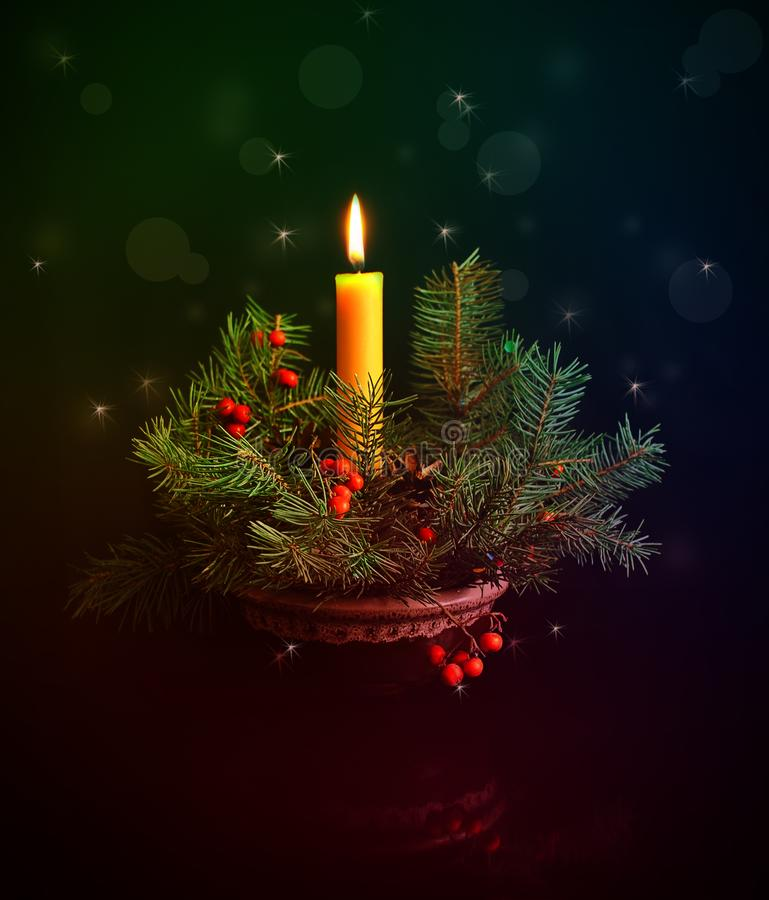 Christmas composition of fir branches and burning candles on a dark background. Composition of fir branches and burning candles on a dark background. Christmas royalty free stock photo