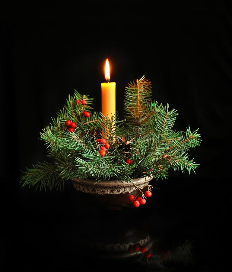 Christmas composition of fir branches and burning candles on a dark background. Composition of fir branches and burning candles on a dark background. Christmas stock photos