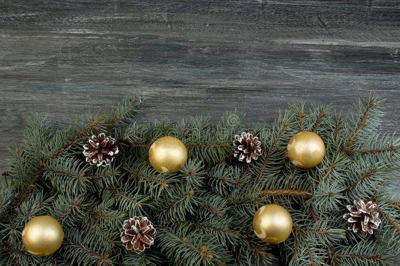 Christmas composition of fir branches and Christmas tree decorations on a wooden background . Top view with copy space stock photography