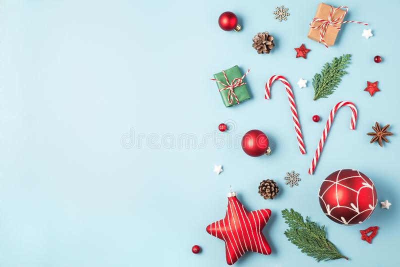Christmas composition. Fir tree branches, gift boxes, red decorations, candy, pine cones on blue background stock photo