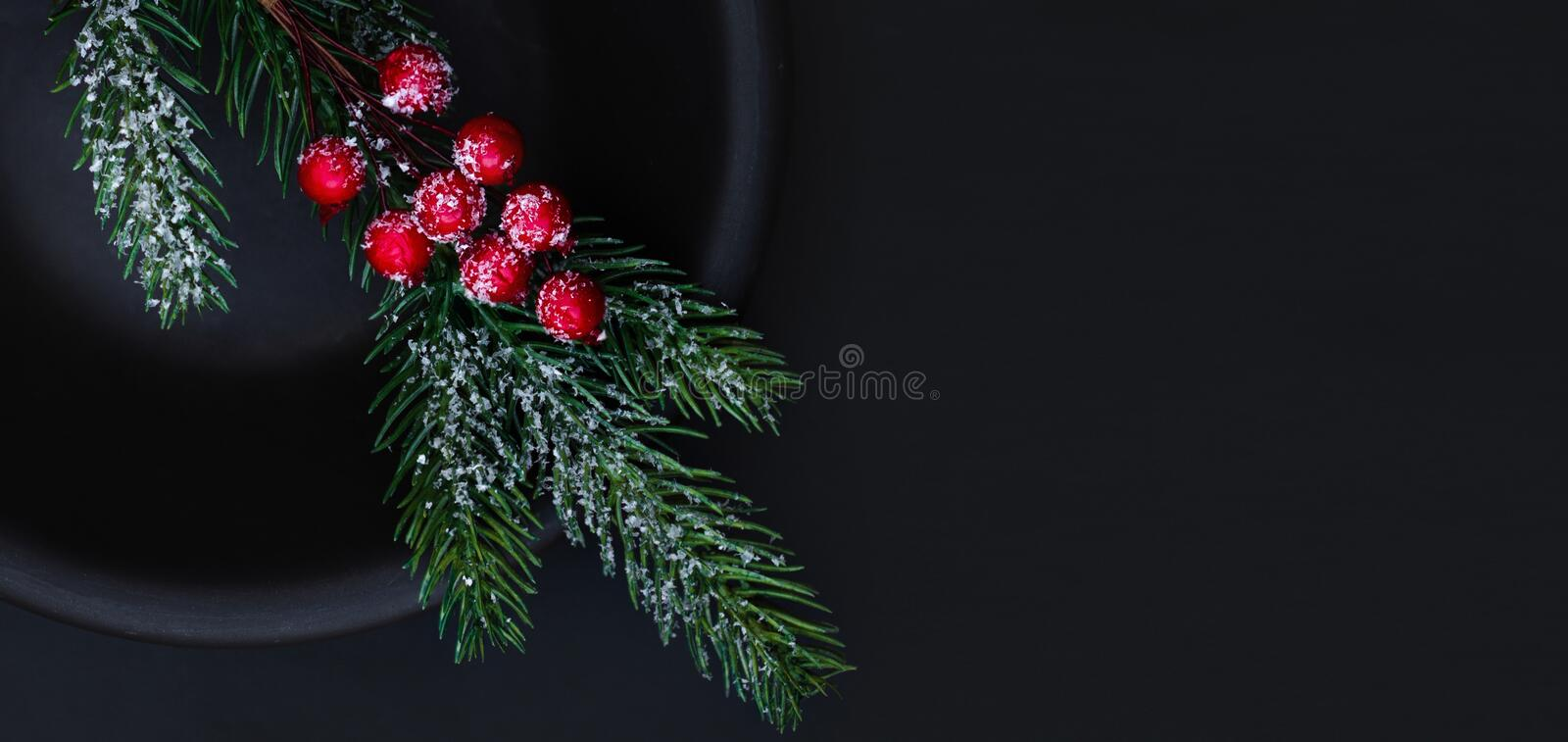 Christmas composition with fir tree and red berries  on dark  background. Xmas tree, pine, winter festive Card. Top view. royalty free stock photography