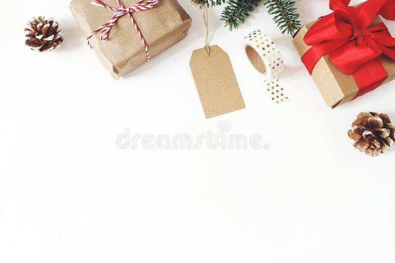 Christmas composition. Frame of fir tree branches, pine cones, christmas gift boxes, tag, golden washi tape, ribbons on stock photos