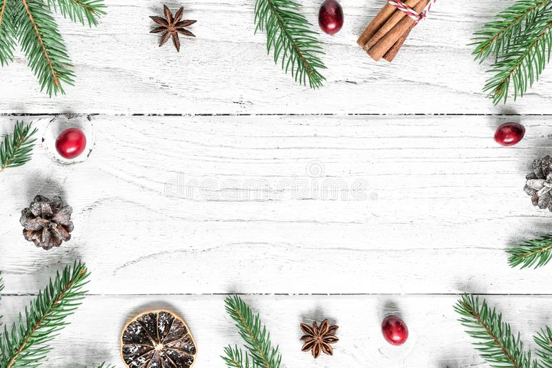 Christmas composition. frame made of fir branches, red berries, star anise and pine cones on white wooden table royalty free stock image