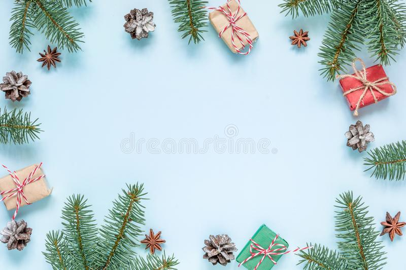 Christmas composition. frame made of fir branches, star anise, decorations, gift boxes and pine cones on blue background stock photos