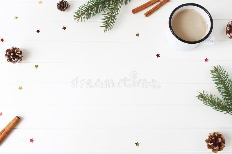 Christmas composition. Frame made of fir, spruce branches, pine cones, cinnamon sticks and glittering confetti stars on royalty free stock photography