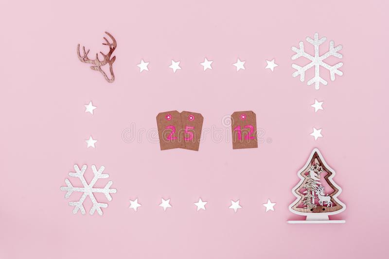 Christmas composition. Frame from white stars, snowflakes, chrismas tree and symbol of deer on pastel pink paper background. Date royalty free illustration