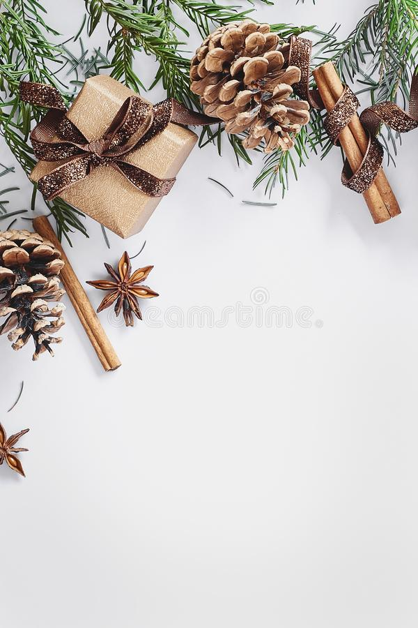 Christmas and New Year composition. Gift box with ribbon, fir branches with cones, star anise, cinnamon on white background royalty free stock image
