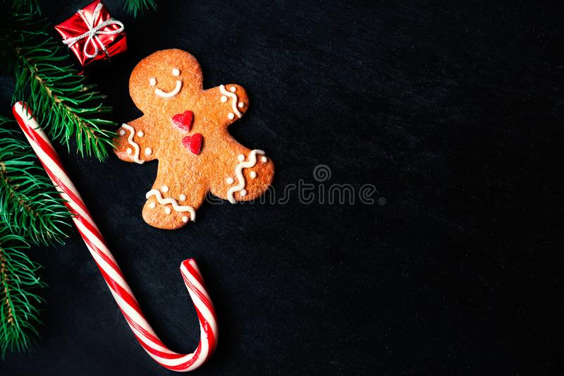Christmas composition with Christmas gift, gingerbread man cookie, fir tree branches, xmas holiday decorations and festive symbol royalty free stock images