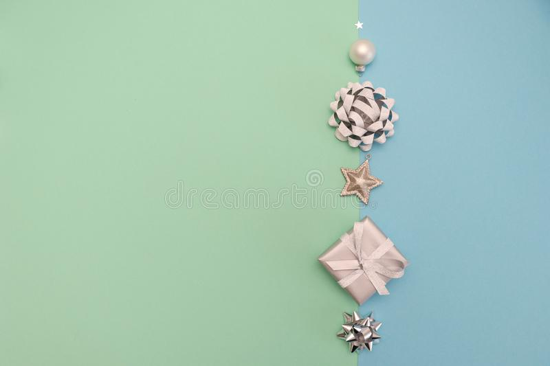 Christmas composition with gift or present boxes, bows, tree ornaments, silver stars on pastel color background, table top view, f stock photography