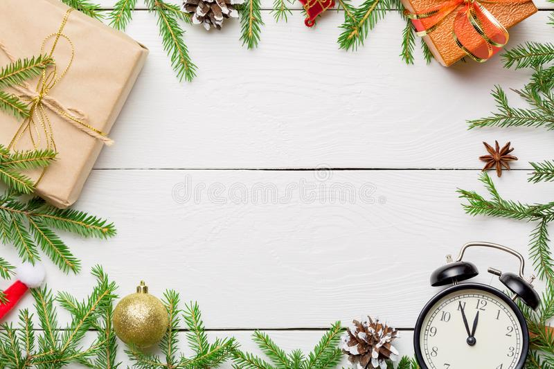Christmas composition. Christmas gifts, pine branches, toys, vintage clock, anise stars, santa hat on wooden white background with stock photo