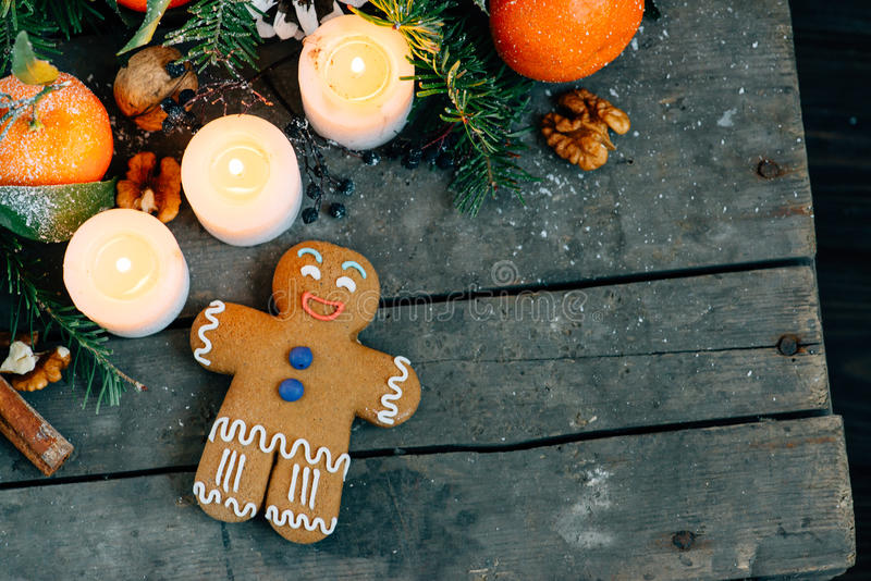 Christmas composition with gingerbread man Tangerines, Pine cones, Walnuts and Candles on Wooden Background, holiday decoration stock photo
