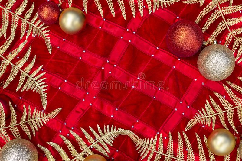 Christmas composition - gold decorations, shiny leaves and branch fern on red background. Flat lay, top view royalty free stock image