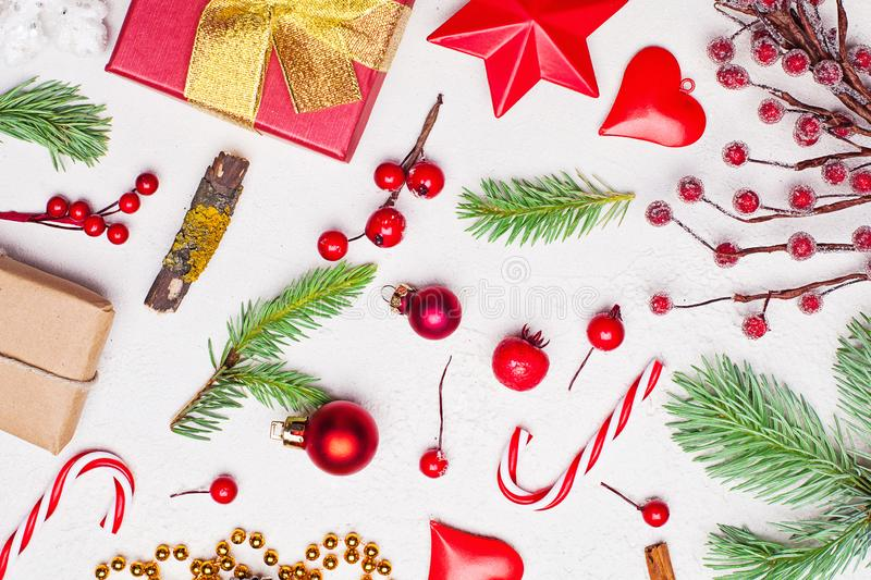Christmas composition with golden garland, red gift, green Xmas fir branch, red holly berries and baubles on white stucco plaster royalty free stock image