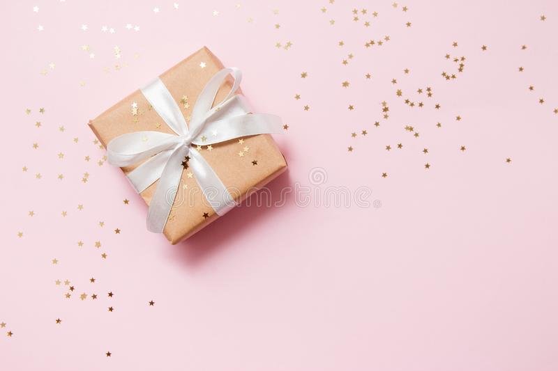 Christmas composition greeting card. Gift from craft paper on a pink background with a gold star confetti. Top view, flat lay royalty free stock images