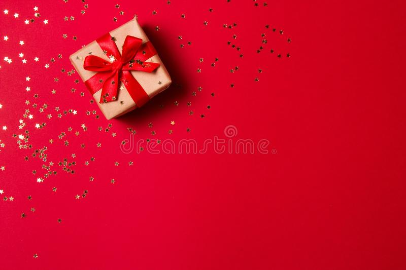 Christmas composition greeting card. Gift from craft paper on a red background with a gold star confetti. Top view, flat lay.  royalty free stock photos