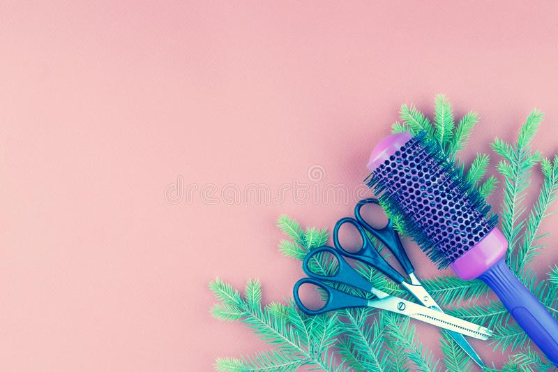Hairdressing tools and spruce branch on a pink background. royalty free stock photography