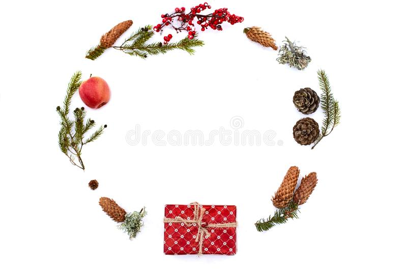 Christmas composition on isolated white background. New year wrapped gift, pine cones, thuja or fir branches, apple and royalty free stock images