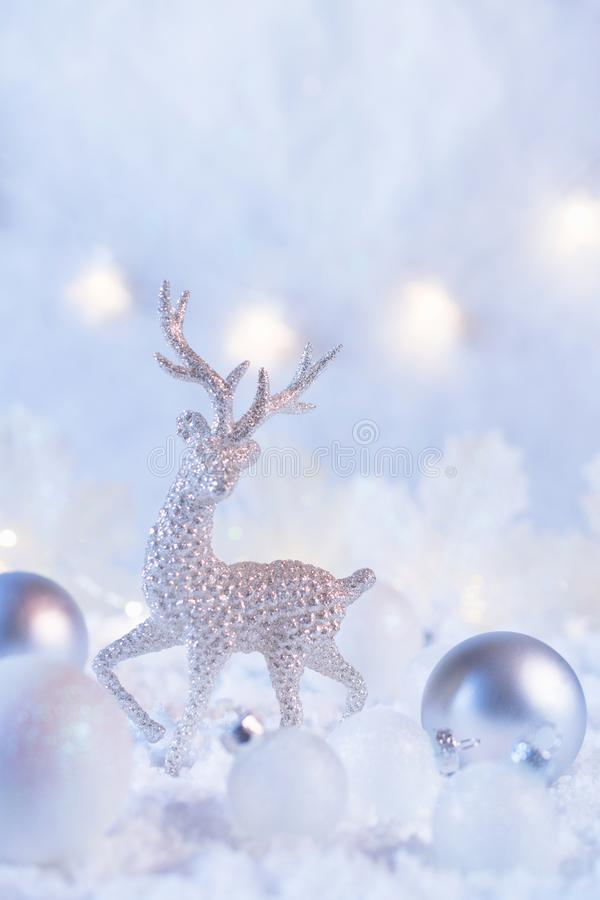 Christmas composition made of Christmas balls and figurine of reindeer on blue winter background. Minimal styled holiday card. stock photo