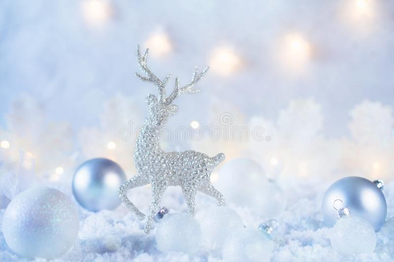 Christmas composition made of Christmas balls and figurine of reindeer on blue winter background. Minimal styled holiday card. royalty free stock photography