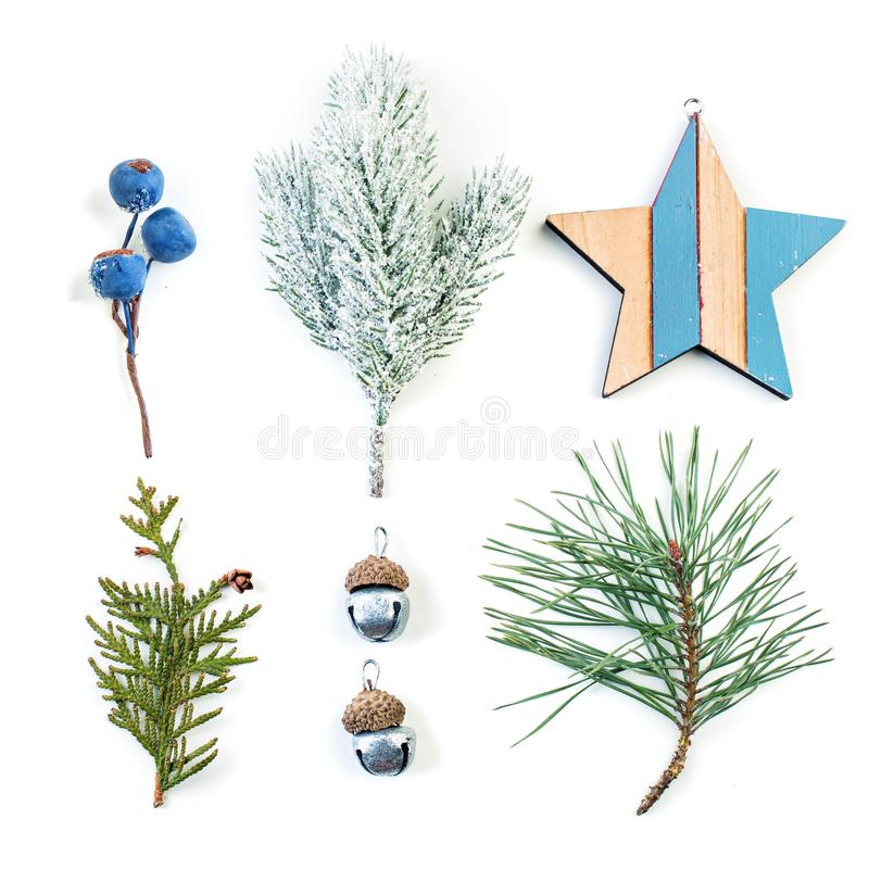 Christmas composition made of natural green and blue decorations. Blue berries, wooden star and green fir branch isolated on white royalty free stock photo
