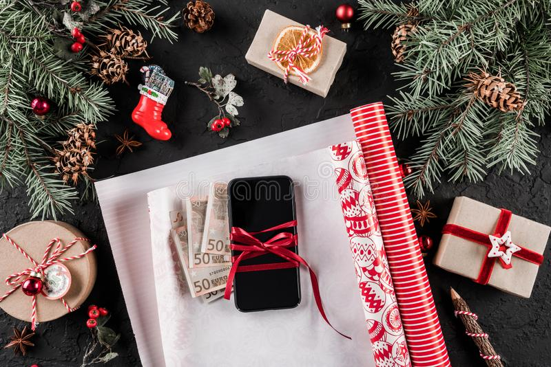 Christmas composition with mobile phone, money, xmas wrapping, Fir branches, gifts, red decorations on dark background. royalty free stock photography