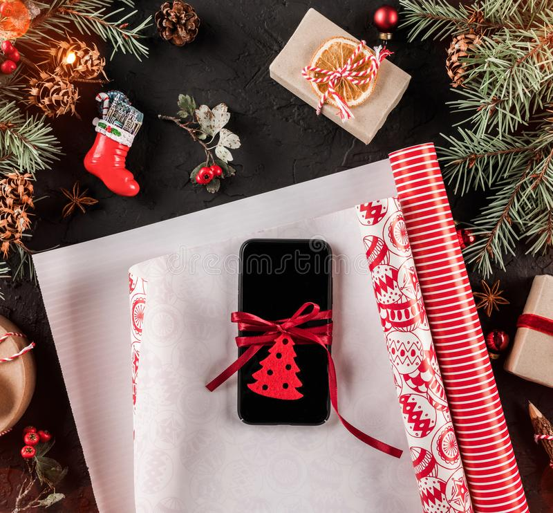Christmas composition with mobile phone, xmas wrapping, Fir branches, gifts, red decorations on dark background. stock photo