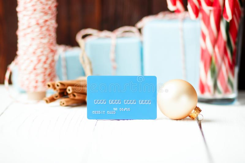 Christmas composition New Year selling discount concept blue credit card with xmas gifts sweets toys balls rope cinnamon on whit royalty free stock photos