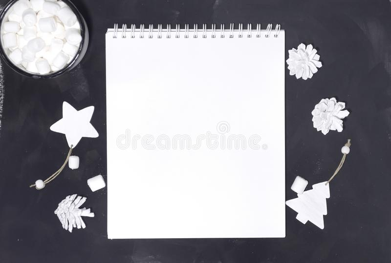Christmas composition. Notebook mockup with white decorations on black background. Christmas, winter, new year concept. Flat lay, royalty free stock photo
