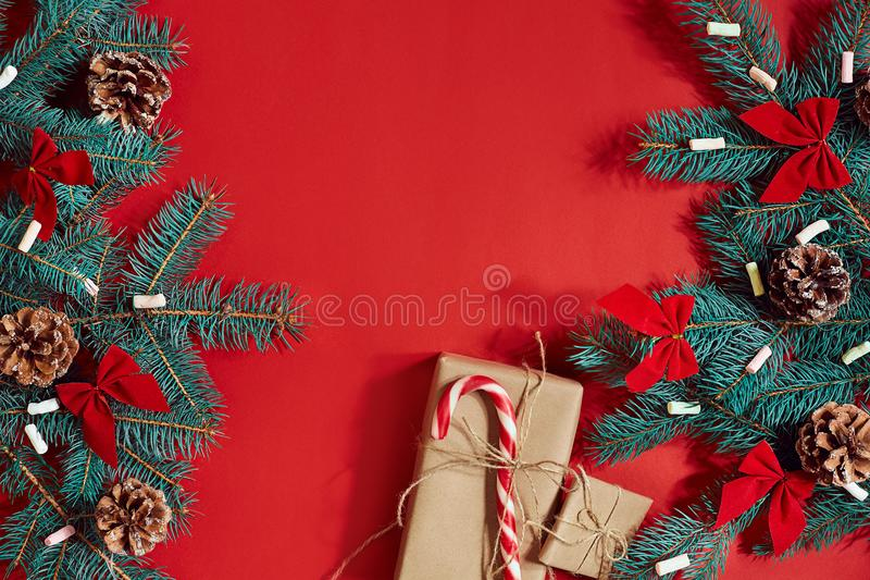 Christmas composition of pine cones, spruce branches and stack of gift boxes on red background stock photos