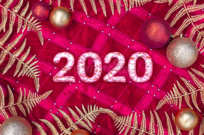 Christmas composition - pink white marble numbers 2020, gold decorations, shiny leaves branch fern on red background. Greeting stock photos
