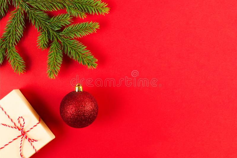 Christmas composition on red background. Green fir tree branches, Xmas present box and decoration. stock photo