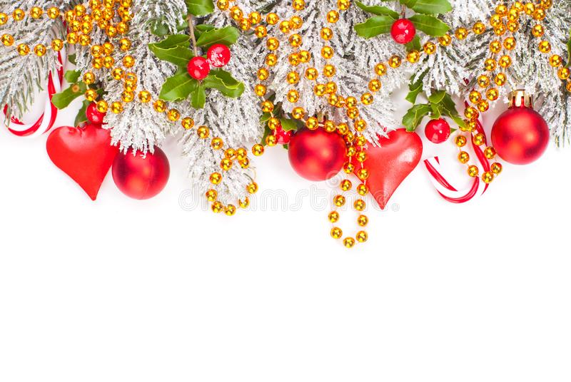 Christmas composition with red holly berries, glass baubles, golden garland and green Xmas tree branch isolated on white stock photos