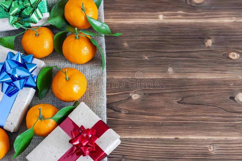 Christmas composition with ripe tangerines, gift box and space for text on wooden background, flat lay stock photos