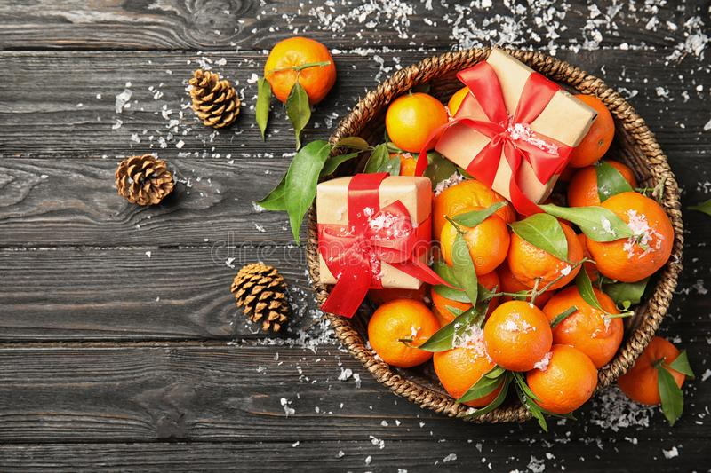 Christmas composition with ripe tangerines, gift boxes and space for text on wooden background. Flat lay royalty free stock images