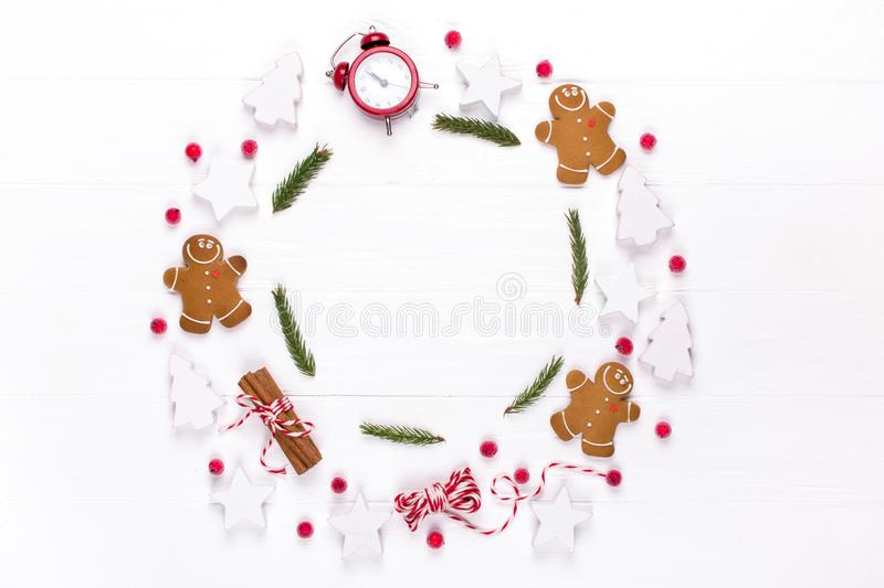 Christmas composition. Round frame made of decorations, fir tree branches, gingerbread man cookies on white background. Winter ho stock photography