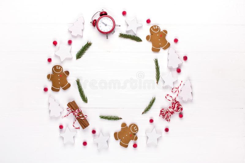 Christmas composition. Round frame made of decorations, fir tree branches, gingerbread man cookies on white background. Winter ho royalty free stock photo